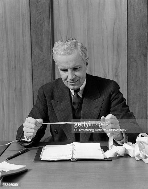 1950s SMILING SENIOR BUSINESSMAN IN SUIT AND TIE SITTING BEHIND DESK READING STOCK MARKET TICKER TAPE
