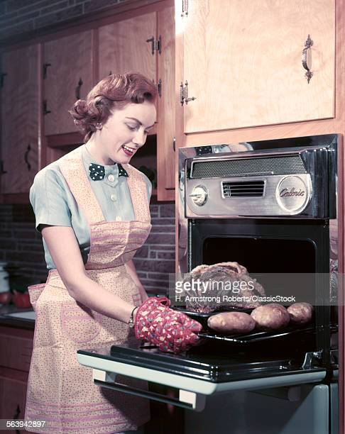 1950s SMILING WOMAN HOUSEWIFE WEARING APRON AND OVEN MITTS TAKING ROAST BEEF WITH POTATOES OUT OF KITCHEN OVEN