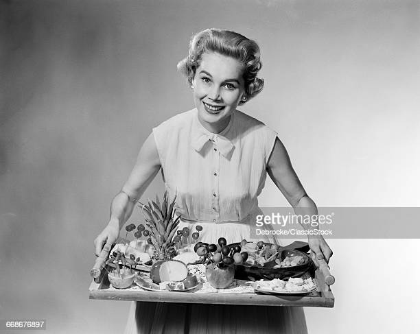 1950s SMILING WOMAN HOSTESS HOLDING TRAY OF FRUIT CHEESE CANAP?S HORS DOEUVRES PARTY FOOD