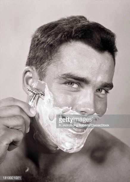 1950s Smiling Young Man Looking At Camera Shaving Face Using A Safety Razor And Shave Cream.