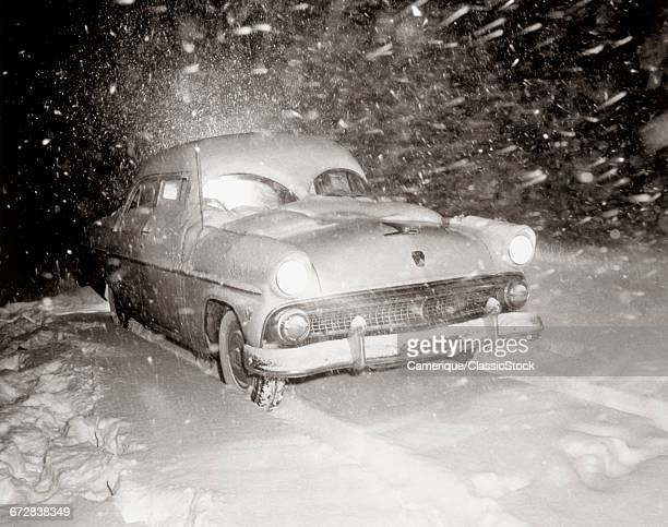 1950s SNOW COVERED AUTOMOBILE DRIVING ON ROAD IN DEEPENING WINTER BLIZZARD SNOW