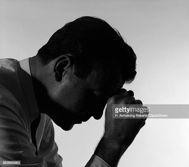 1950s SOLITARY ANONYMOUS DEPRESSED SAD WORRIED SILHOUETTED MAN HEAD DOWN HAND TO FOREHEAD