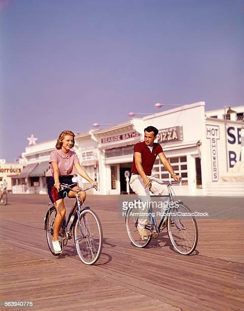 1950s TEEN COUPLE RIDING...