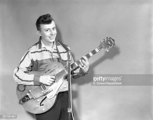 1950s TEENAGE BOY SINGING PLAYING GUITAR INTO MICROPHONE LOOKING AT CAMERA