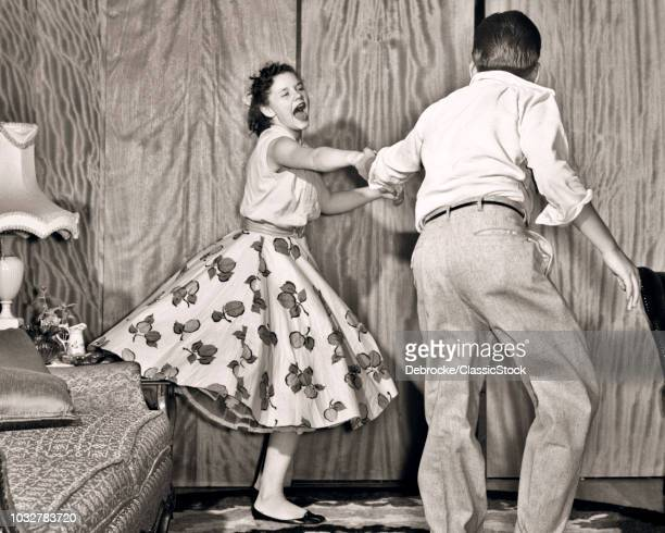 1950s TEENAGE COUPLE BOY AND GIRL DANCING ROCK AND ROLL JITTERBUG