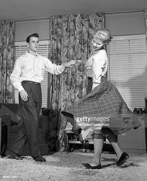 1950s TEENAGE COUPLE JITTERBUG DANCING TOGETHER IN LIVING ROOM