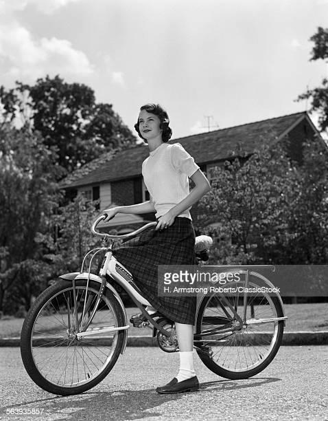 1950s TEENAGE GIRL STANDING WITH BIKE