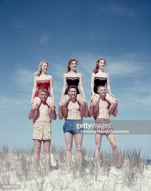 1950s THREE TEENAGE COUPLES STANDING ON SAND DUNE GIRLS SITTING ON GUYS SHOULDERS