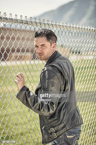 1950s Tough Guy Leaning on a Chain Link Fence
