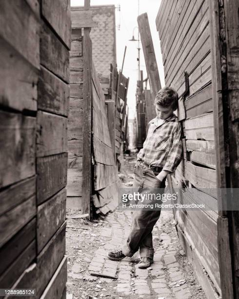 1950s Truancy Sad Lonely Pre-Teen Boy In Poverty Stricken Neighborhood Alley Leaning Up Against A Wooden Fence Playing Hooky
