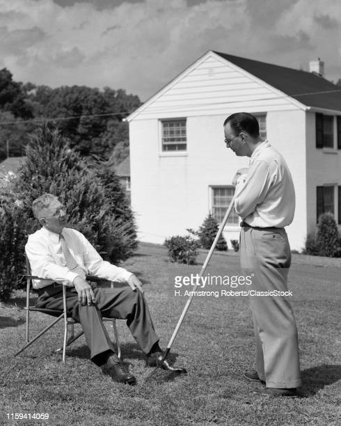 1950s two men in backyard neighbors talking one seated other standing with rake