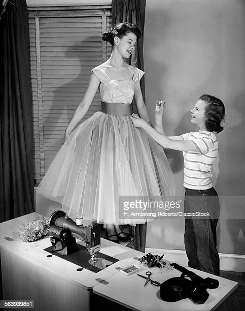 1950s TWO TEEN GIRLS WITH SEWING MACHINE ONE GIRL MODELING FANCY PROM DRESS OTHER GIRL ADJUSTING WAISTBAND