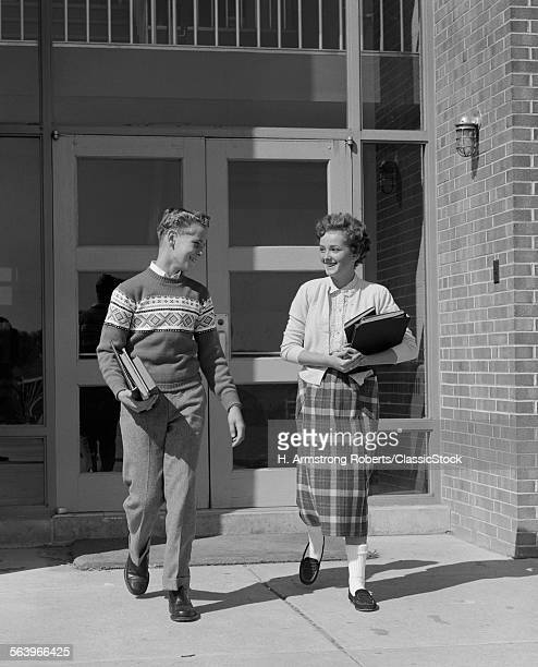 1950s TWO TEENAGE STUDENTS BOY AND GIRL WALKING AWAY FROM SCHOOL DOORS CARRYING BOOKS
