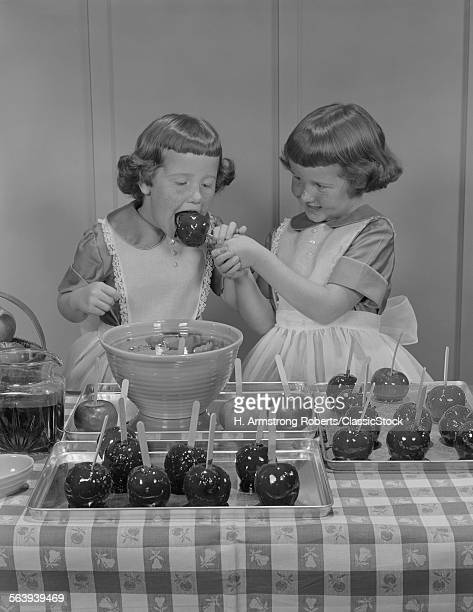 1950s TWO TWIN GIRLS EATING MAKING CANDY APPLES IN KITCHEN