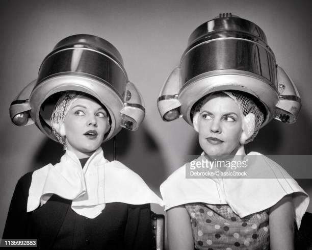 1950s TWO WOMEN SITTING UNDER BEAUTY SALON HAIR DRYERS WEARING HAIRNETS TOWELS TALKING GOSSIP