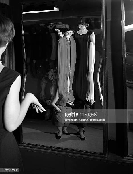 1950s TWO YOUNG WOMEN LOOKING AT DISTORTED REFLECTION IN FUN HOUSE MIRROR