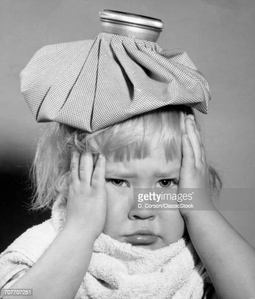 1950s UNHAPPY LITTLE BLONDE GIRL ICE PACK ON HEAD HANDS SIDE OF FACE TOWEL WRAPPED AROUND NECK FEVER HEADACHE SORE THROAT MUMPS
