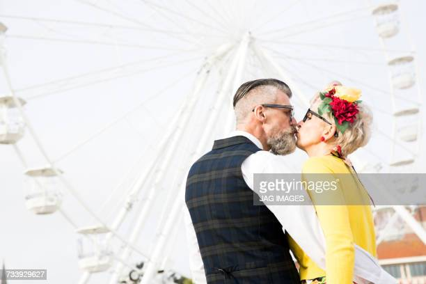 1950s vintage style couple kissing in front of ferris wheel