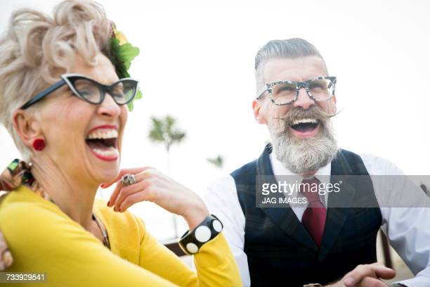 1950s vintage style couple laughing together at coast - freaky couples stockfoto's en -beelden