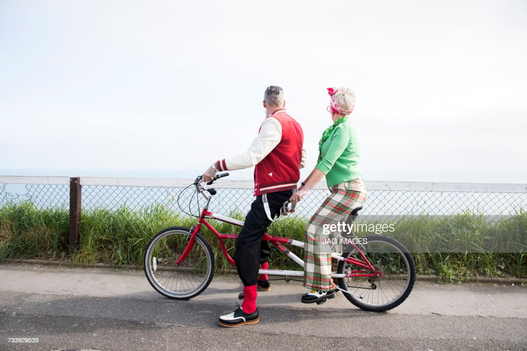 1950s vintage style couple looking out from tandem bicycle at coast : Stock Photo