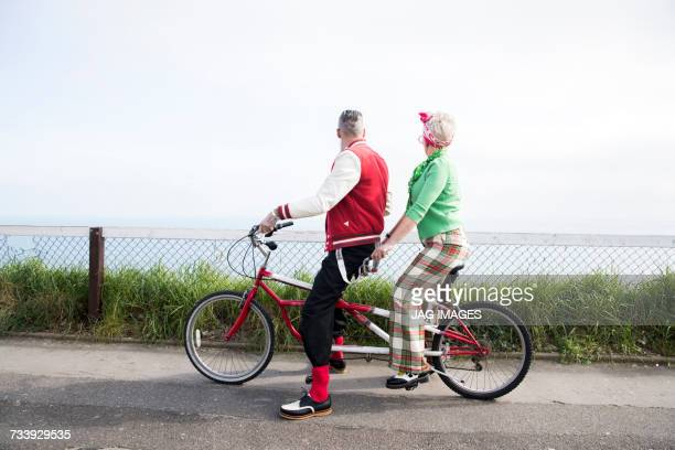 1950s vintage style couple looking out from tandem bicycle at coast