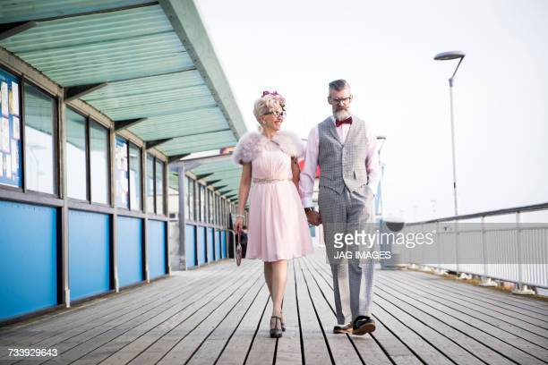 1950s vintage style couple strolling and holding hands on pier
