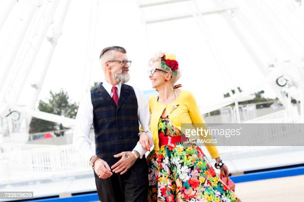 1950s vintage style couple strolling in front of ferris wheel