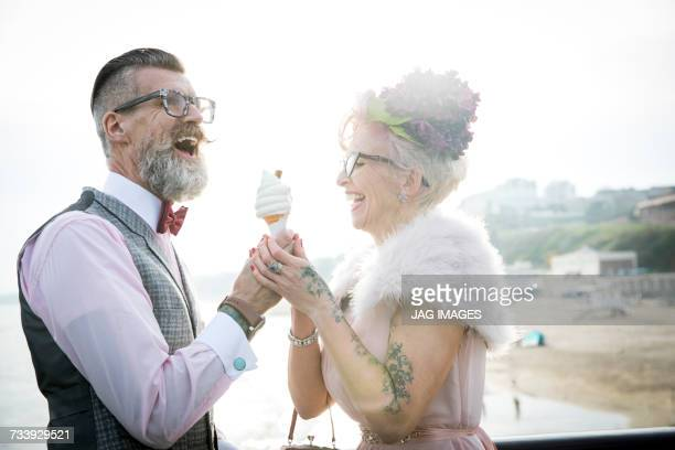 1950s vintage style couple with ice cream cone, laughing on pier - offbeat stock pictures, royalty-free photos & images