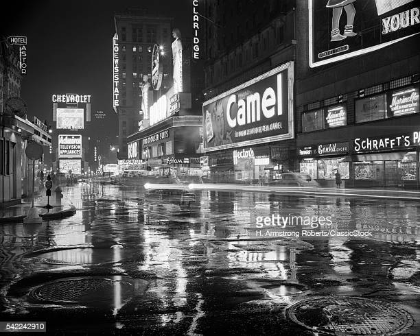 1950s WET RAINY STREETS OF TIMES SQUARE AT NIGHT NEON SIGNS ADVERTISING NEW YORK CITY NY USA