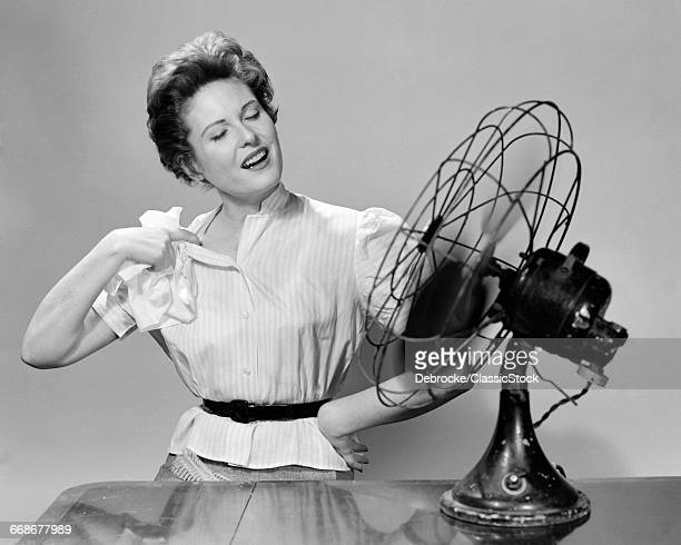 1950s WOMAN COOLING WITH...
