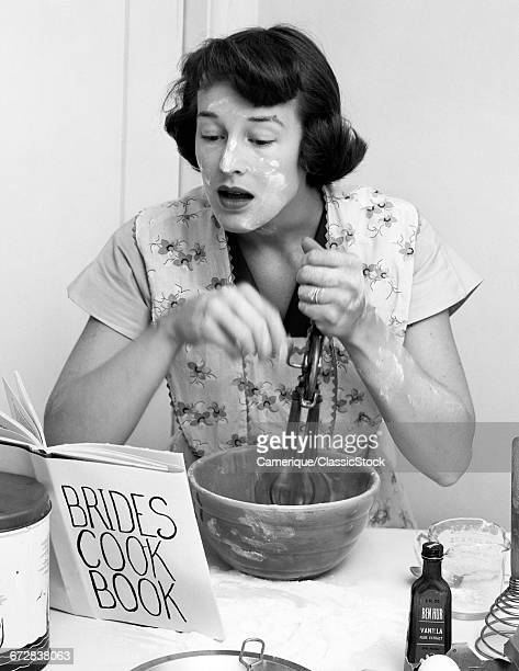 1950s WOMAN FACE COVERED FLOUR MIXING INGREDIENTS READING BRIDES COOK BOOK