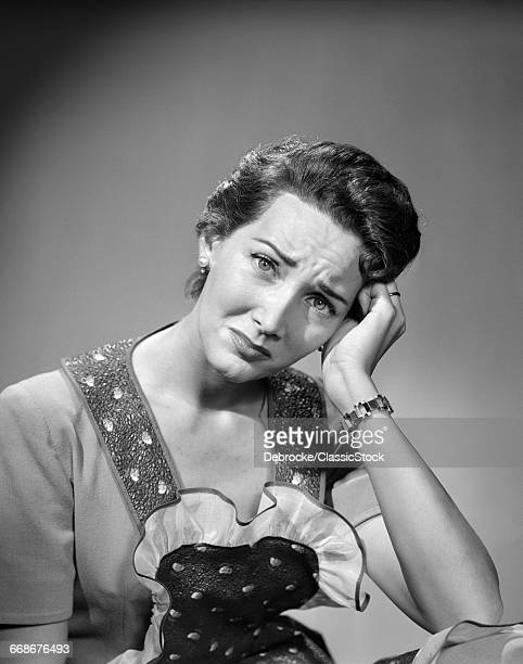 1950s WOMAN HOUSEWIFE IN APRON LOOKING AT CAMERA HAND UP TO TEMPLE HEADACHE PAIN SAD DEPRESSED SERIOUS FACIAL EXPRESSION WORRIED