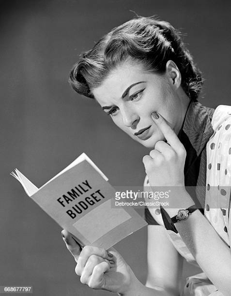 1950s WOMAN IN APRON FINGER ON CHEEK LOOKING AT FAMILY BUDGET BOOK