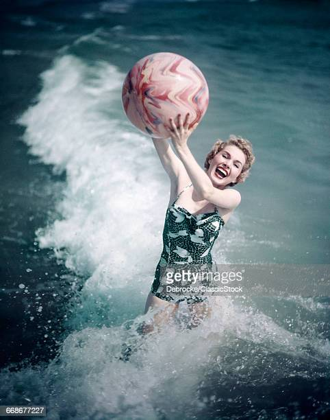 1950s WOMAN JUMPING IN SURF HOLDING UP BEACH BALL