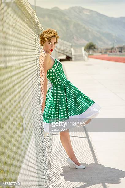 1950s woman leaning on a chainlink fence making kissing face - poodle skirt stock photos and pictures