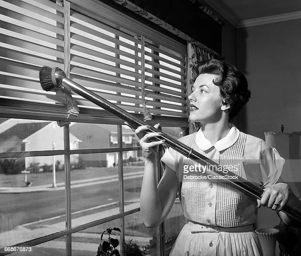 1950s WOMAN VACUUMING VENETIAN BLINDS ON WINDOW LOOKING OUT ONTO SUBURBAN STREET