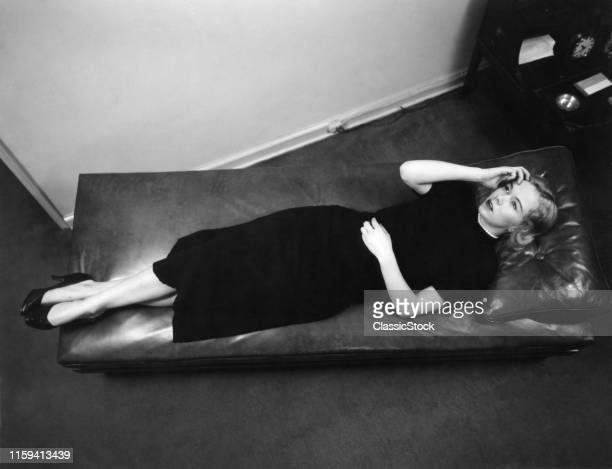 1950s WORRIED WOMAN HAND TO FOREHEAD SEEN FROM ABOVE LYING DOWN ON PSYCHIATRIST THERAPY COUCH