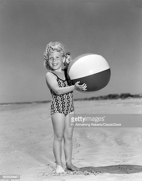 1950s SMILING LITTLE GIRL STANDING ON BEACH HOLDING BEACH BALL LOOKING AT CAMERA