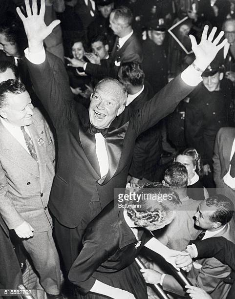 New York, NY: Soldier, statesman and now President-elect General Ike Eisenhower flashes a winning smile as he raises his arms in a familiar gesture...