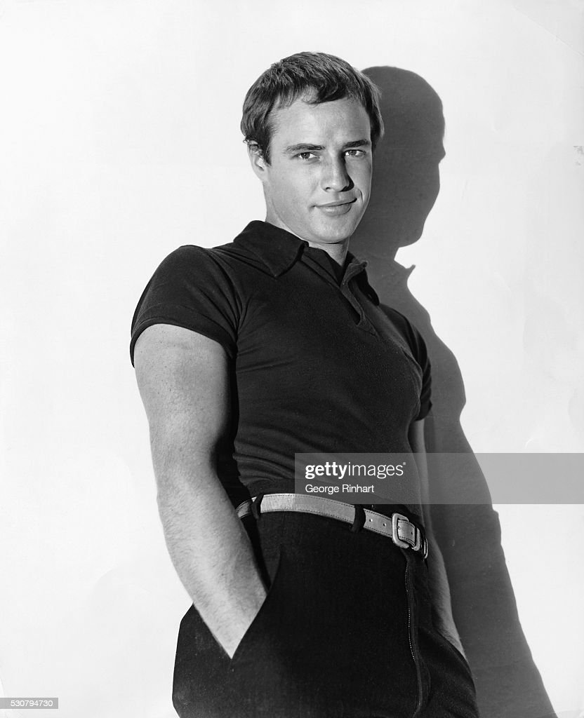 Publicity photograph of famed actor Marlon Brando (1924- ), leaning against a white wall.