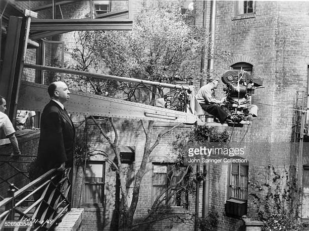 Director Alfred Hitchcock observes the action from a balcony as cameramen extended out on an arm film a scene on the set of Rear Window 1954