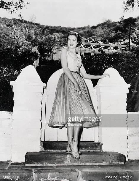 1954Grace Kelly models an Edith Head designer dress by a garden gate Photo 1954 Kelly is appearing in the Hitchcock film Rear Window
