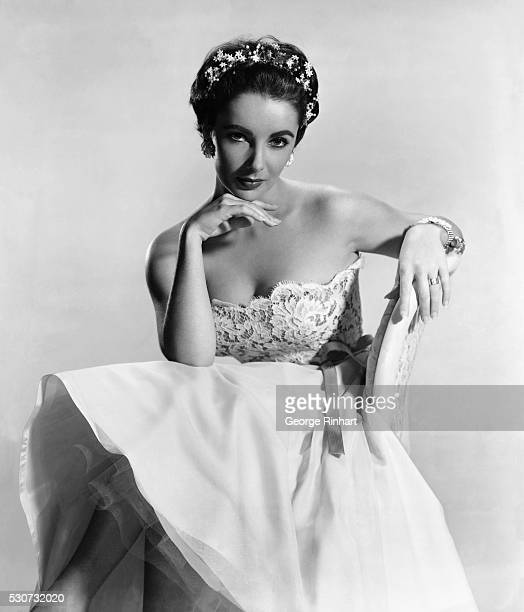 Actress Elizabeth Taylor is shown seated, wearing a wedding gown-like dress and a pretty tiara.