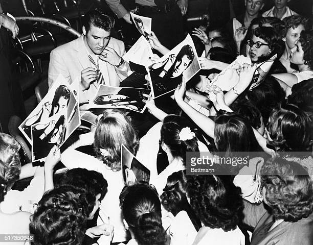 Elvis Presley, American singer surrounded by his enthusiastic teenage fans.