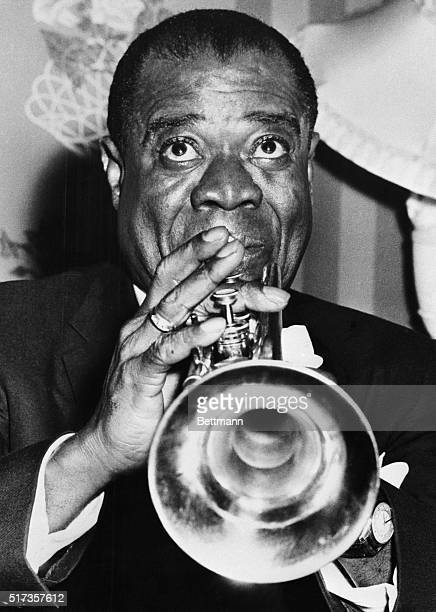 London- Famed jazz trumpeter Louis Armstrong is back in Britain after a lapse of 21 years. Armstrong is seen here at a reception at the Savoy Hotel,...