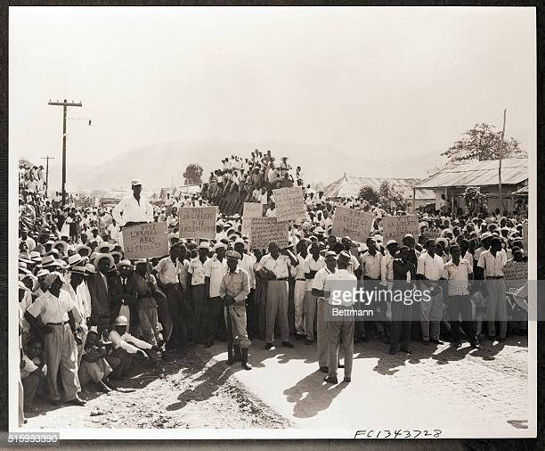 1957Saint Marc HaitiA crowd of placardcarrying demonstratos are shown gatherd in protest against the sevenman executive coucil which ruled Haiti...