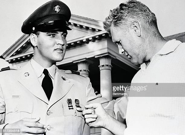Memphis, Tennessee: Vernon Presley, Elvis Presley's father, looks like any other proud parent as he examines his sons medals, in front of the Presley...