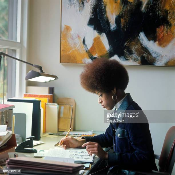 1960s 1970s African American Woman Student Sitting At Desk Writing By Window Denim Jacket.