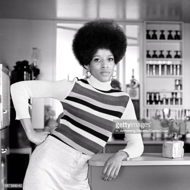 1960s 1970s African-American Woman Tall Afro Hairstyle Striped Shirt Leaning On Restaurant Counter Hand On Hip Looking At Camera