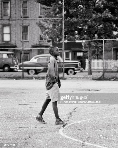1960s 1970s Anonymous Alone African-American Young Man Walking Across Asphalt City Playground Hands In Pockets NYC USA